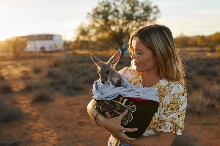 Halten eines Baby-Kängurus im The Kangaroo Sanctuary, Alice Springs, Northern Territory © Tourism NT/Matt Cherubino 2019