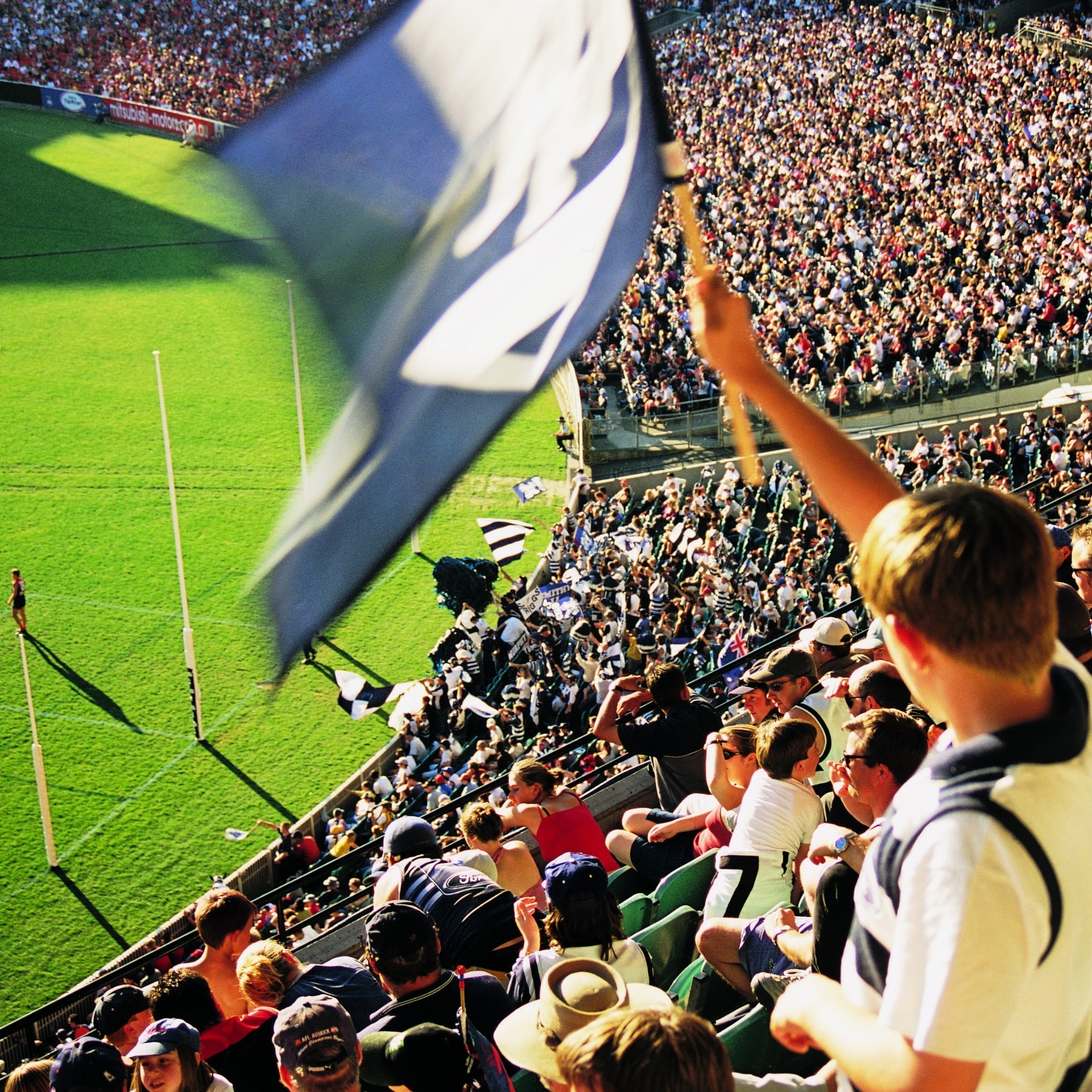 Fan waves flag at the AFL grand final in Melbourne © Tourism Victoria