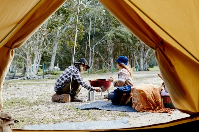 Couple cooking over the barbecue outside their tent on Noosa's North Shore © Tourism and Events Queensland/Ming Nomchong