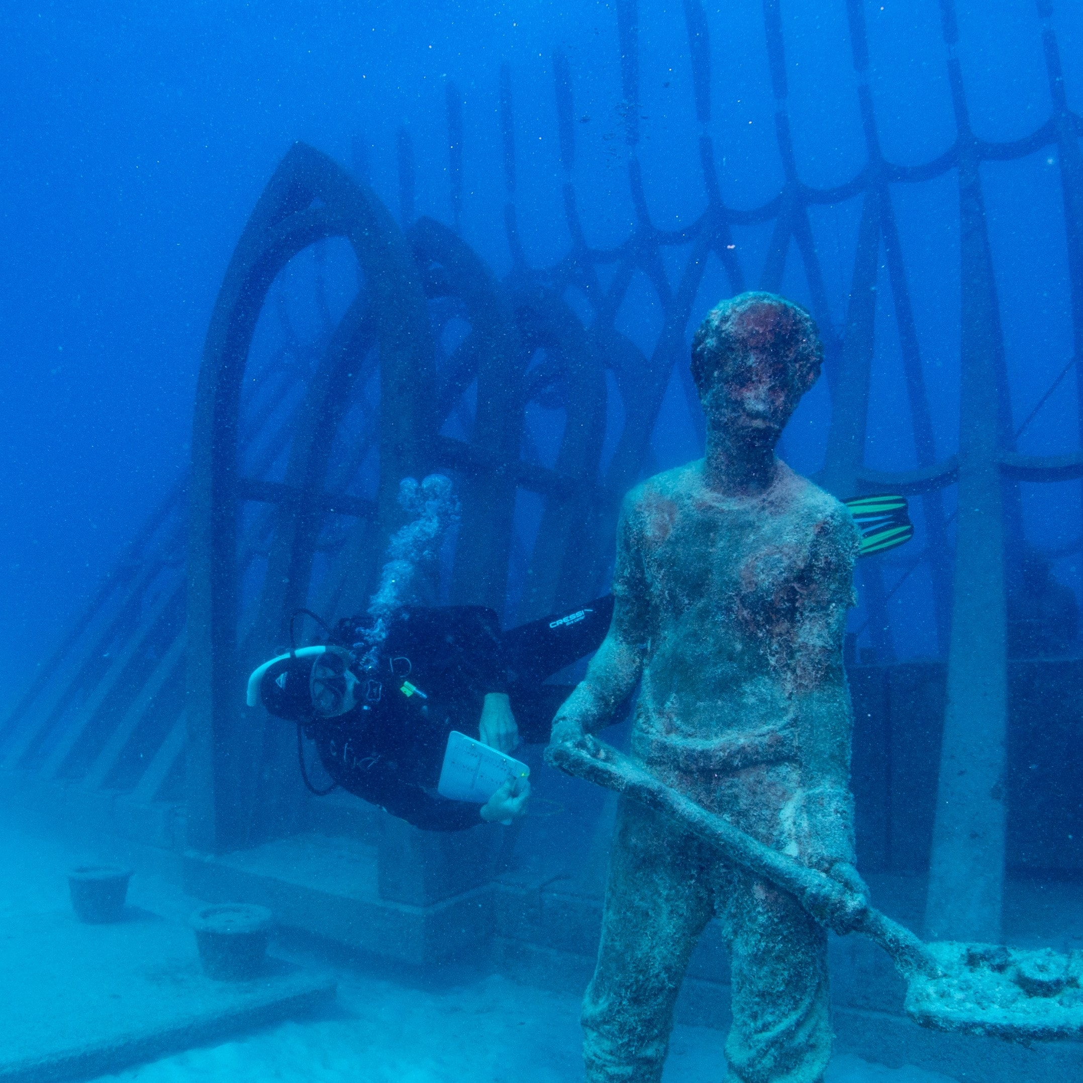 Scuba diver swims next to an exhibit at the Museum of Underwater Art in Townsville © Gemma Molinaro Photography