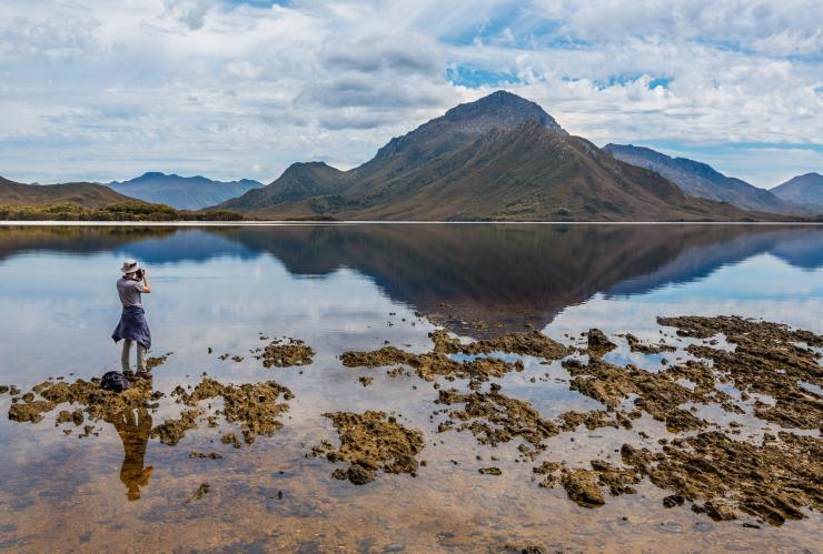 A man taking a picture of the scenic views in Southwest National Park in Tasmania © Par Avion/Paul Fleming