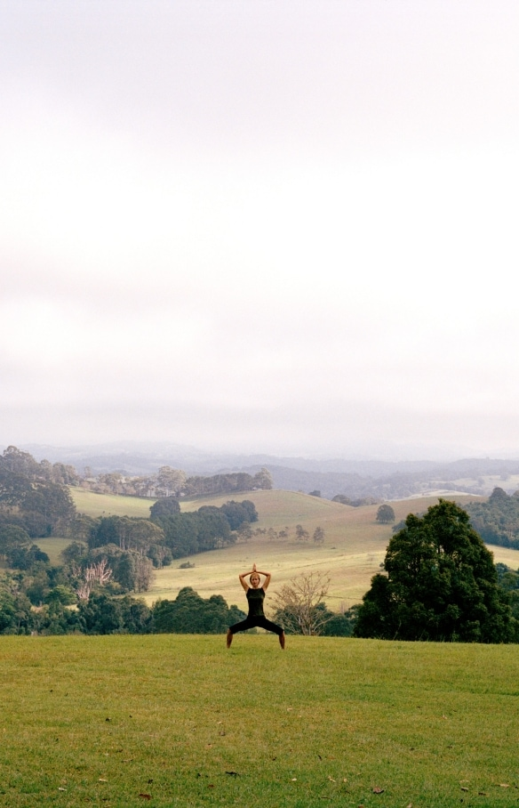 Woman doing a yoga pose on the grass at Gaia Retreat and Spa © Tourism Australia