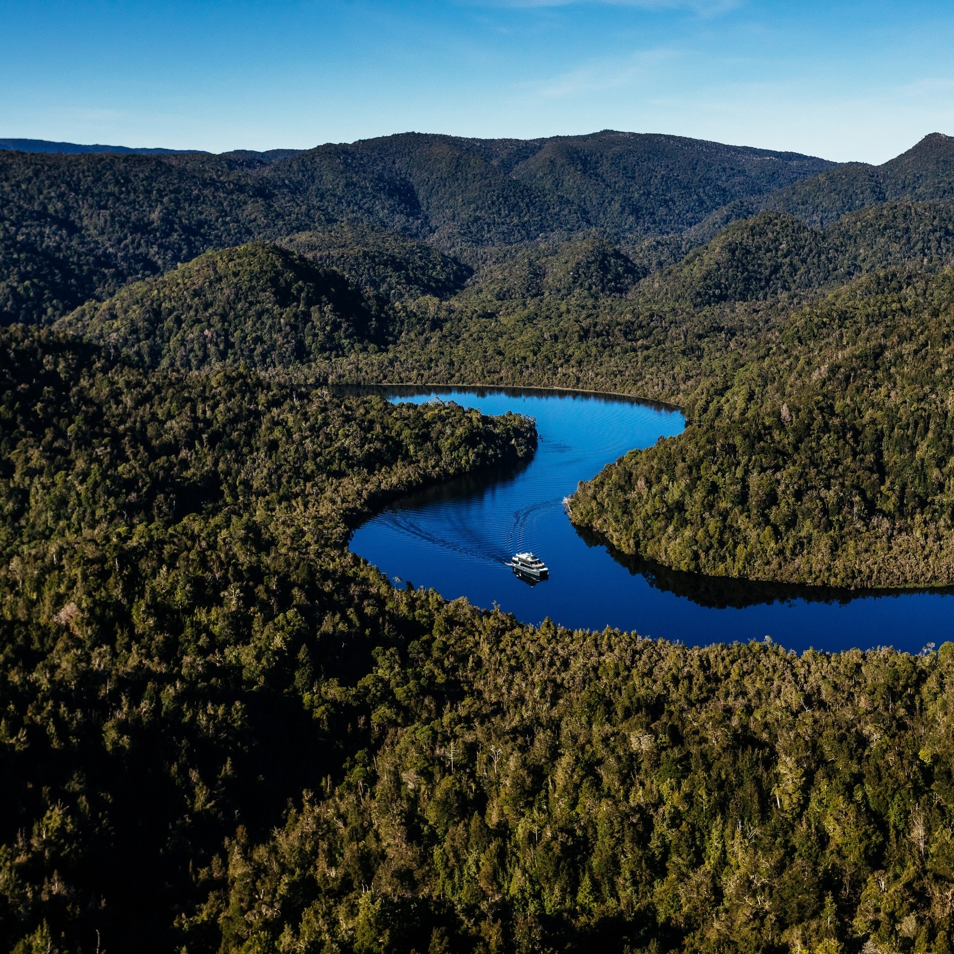 A boat cruising down Gordon River in Franklin-Gordon Wild Rivers National Park © Tourism Tasmania