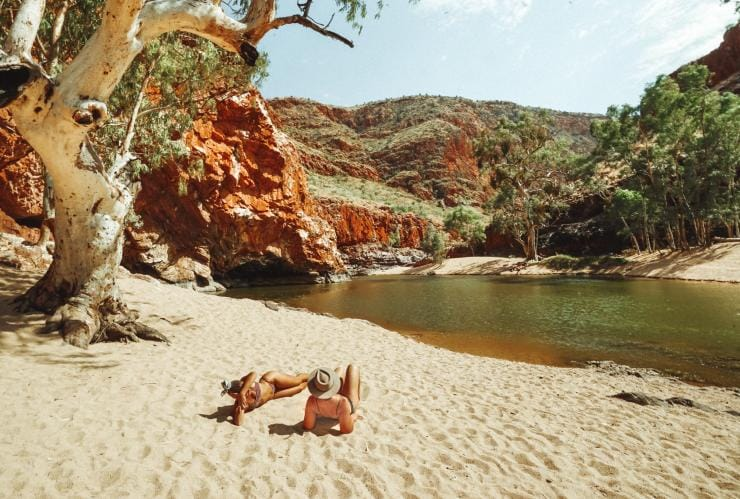 Two friends relax on the sand next to the water at Ormiston Gorge © Tourism NT/Jackson Groves