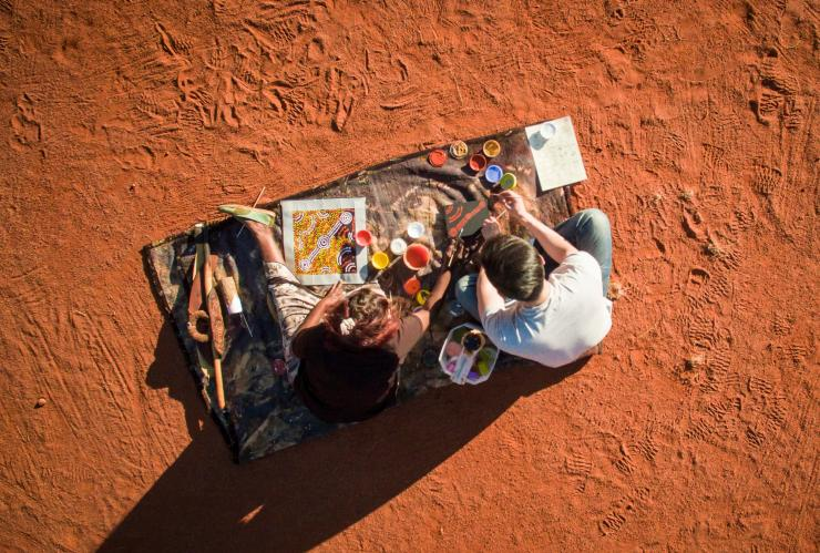 View from above of a visitor learning dot painting with a local Aboriginal artist from Maruku Arts near Uluru in the Northern Territory © Tourism NT/Archie Sartracom