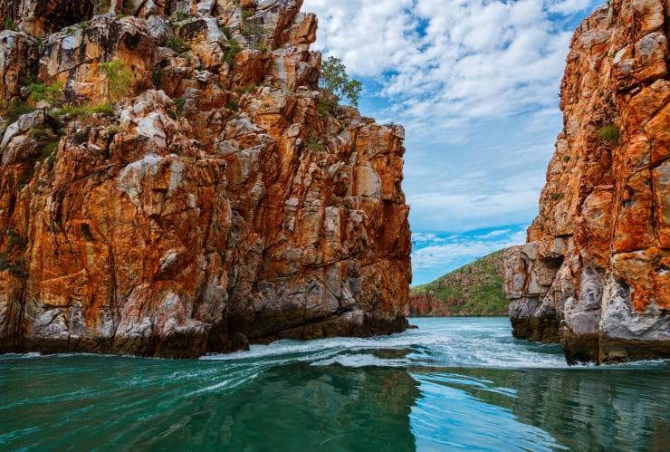 View from a boat passing through the red rocks of Horizontal Falls in the Kimberley Region © Lauren Bath
