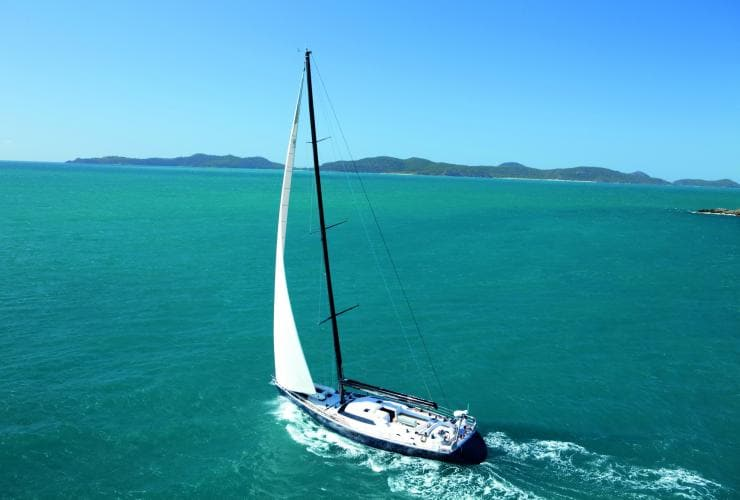 Aerial view of a sailboat on blue water in the Whitsundays © Tourism and Events Queensland