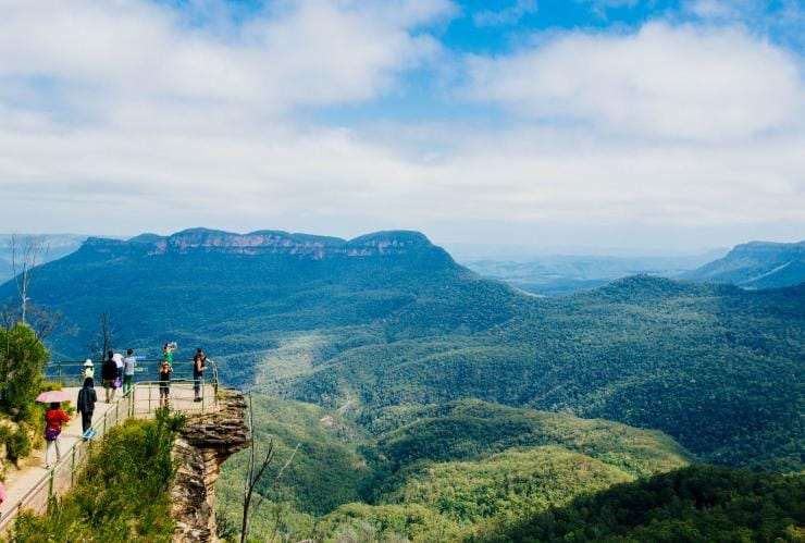 A green valley of the Blue Mountains with the three peaks of the Three Sisters rock formation in view © Destination NSW