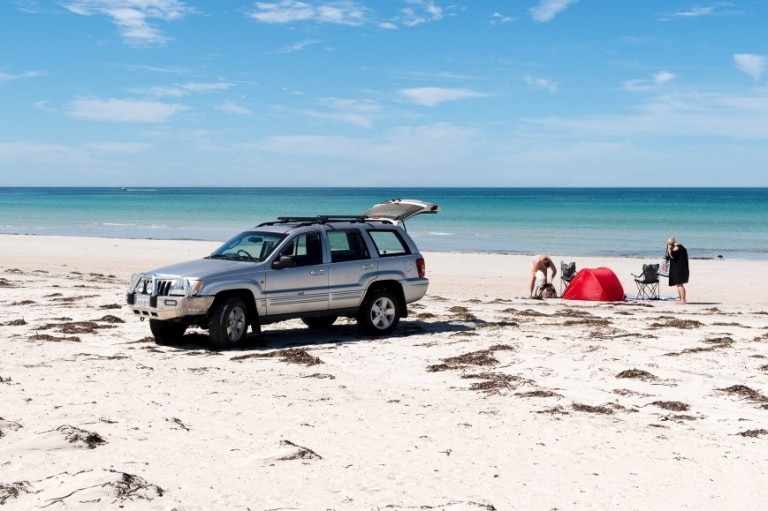 People relaxing on the beach with their car © South Australian Tourism Commission