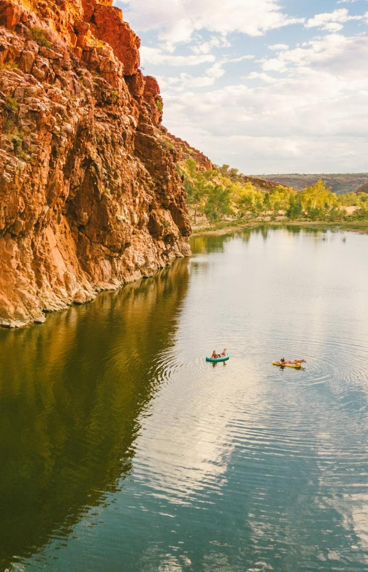 Two women swimming in the calm Glen Helen Gorge next to red cliffs © Tourism NT/Mitchell Cox