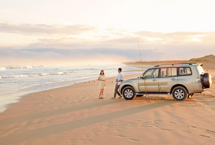 Couple stands near their car on the golden sands of Stockton Beach in Port Stephens © Tourism Australia