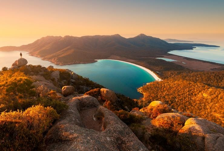 Person stands on a peak overlooking the white, curved beach of Wineglass Bay © Matt Donovan