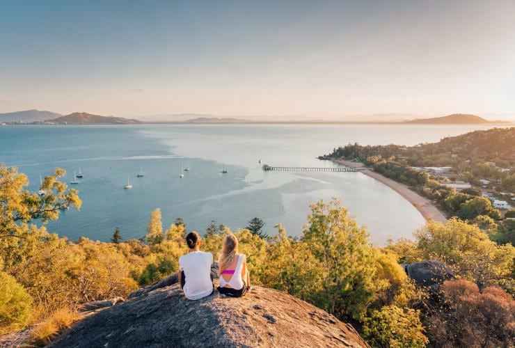 Two girls sat on Hawkins Point looking out to sea © Tourism and Events Queensland
