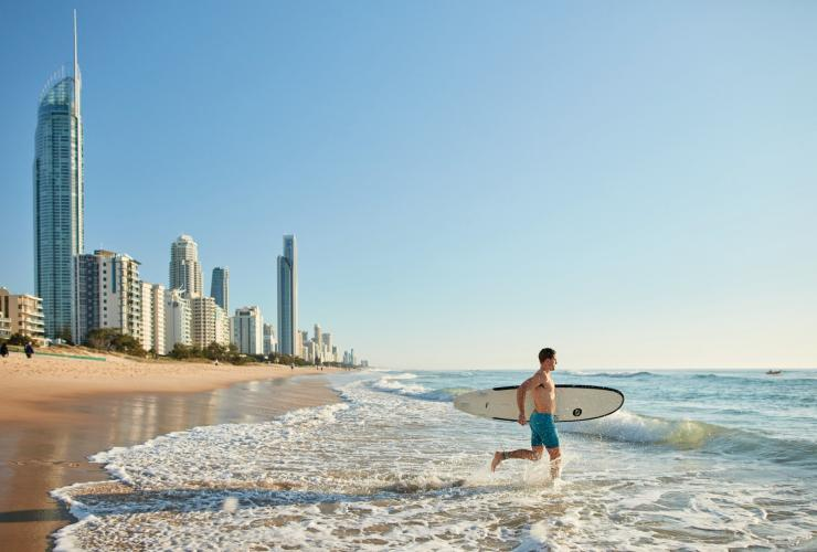 Surfer runs into the ocean with a surfboard on a beach in Surfers Paradise © Matt Harvey/Tourism and Events Queensland