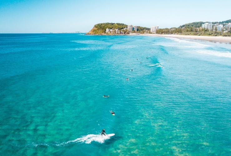 Surfers at North Burleigh beach with a view of Burleigh Headland in the distance © Nathan Prostamo/Tourism and Events Queensland