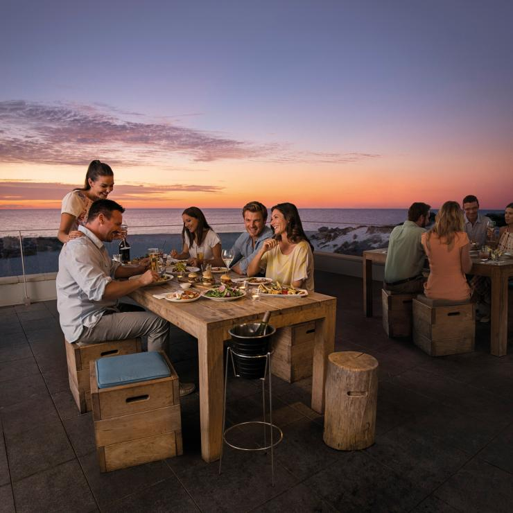 Group of friends dining at Bib and Tucker over sunset © Tourism Australia