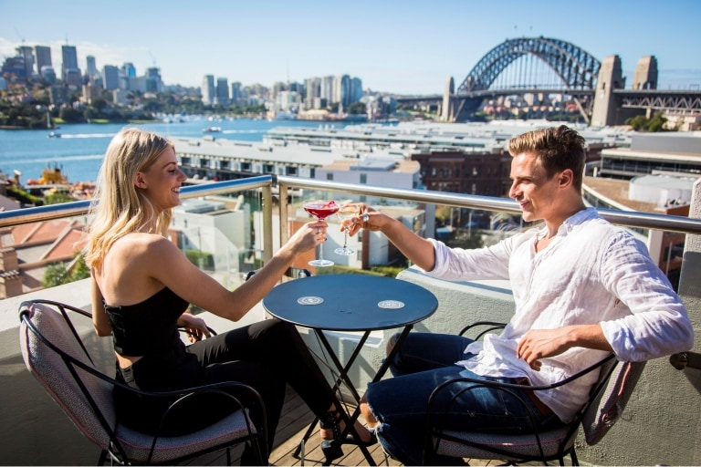 Couple enjoying drinks on the rooftop at Henry Deane in Sydney © Destination NSW
