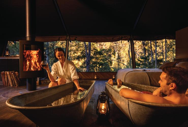 Couple in bathtubs by the fire inside their glamping tent at Nightfall camp  © Nightfall camp