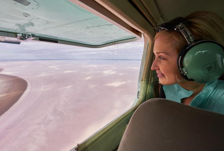 Woman looking out the window on a scenic flight over Kati Thanda-Lake Eyre National Park © South Australian Tourism Commission