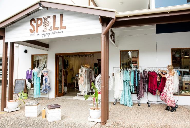 Woman arranging clothes for display at the Spell & The Gypsy Collective in Byron Bay © Destination NSW