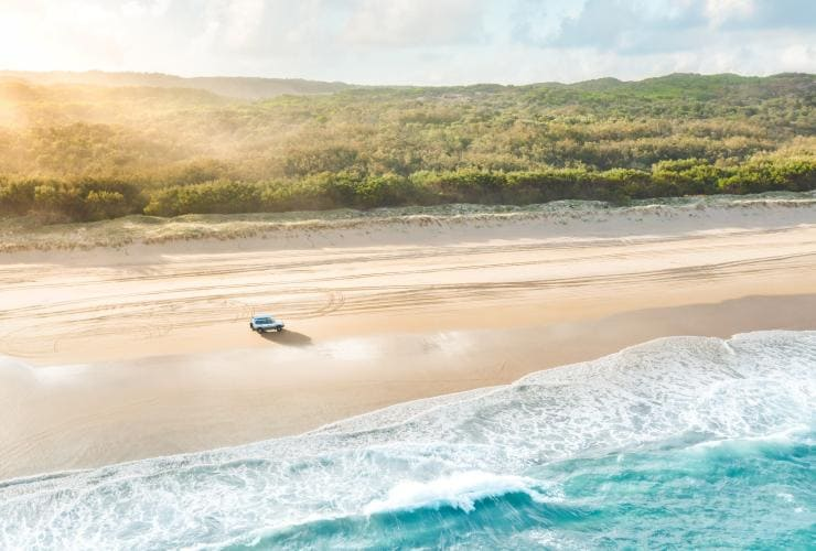 Aerial view of a car driving along the beach on North Stradbroke Island © Tourism and Events Queensland/Jesse Lindemann
