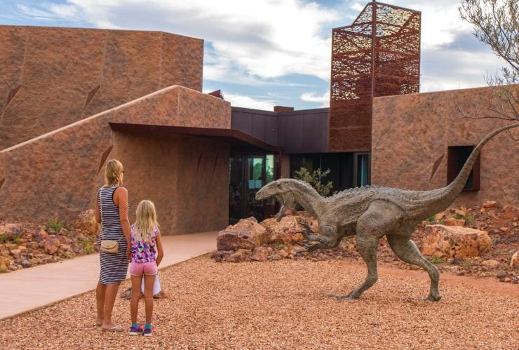 Woman and child looking at a dinosaur statue outside the Australian Age of Dinosaurs Museum © Tourism and Events Queensland