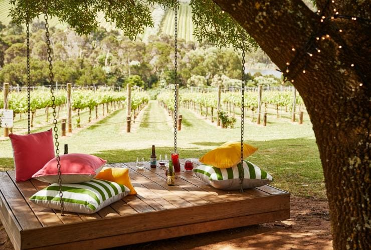 Pillows and drinks on a large wooden swing at Tucks Wine © Griffin Simm