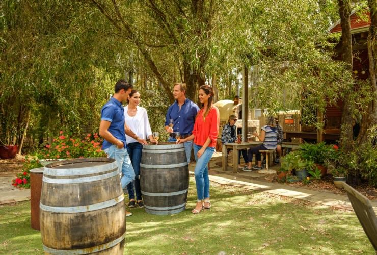 Group of friends enjoying glasses of wine on the lawn at Oranje Tractor Wines © Tourism Western Australia
