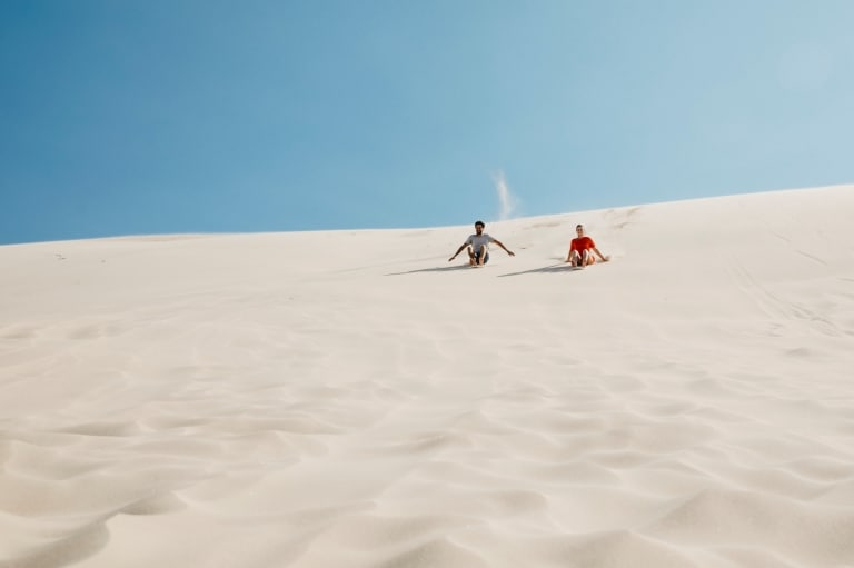 Couple rides down sand dune on a sandboard in Port Stephens © Destination NSW