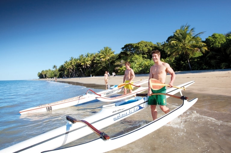 Men pushing boats into the ocean at Four Mile Beach near Port Douglas © Tourism Port Douglas and Daintree