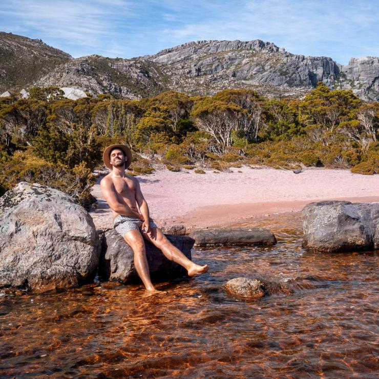 Miles Gray posing on a rock at a lake in West-Coast Tasmania © Miles Gray, @milesuncharted