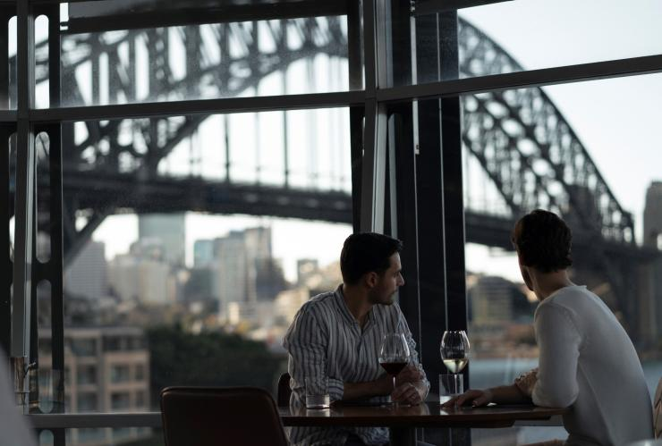 Couple enjoying wine with views across Sydney Harbour towards the Sydney Harbour Bridge from Quay Restaurant © Destination NSW