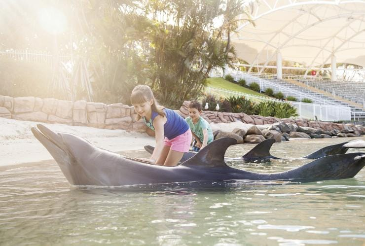 Children interact with dolphins at Sea World on the Gold Coast in Queensland © Sea World