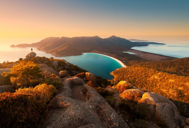 Hiker looks down on Wineglass Bay in Tasmania's Freycinet National Park © Matt Donovan