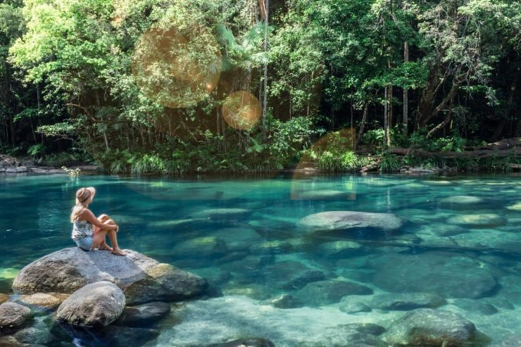 Woman sits on rock beside rockpool at Mossman Gorge © Tourism and Events Queensland