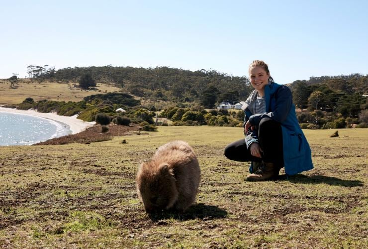 Hiker crouched next to a wombat along the Maria Island Walk  © Tourism Australia