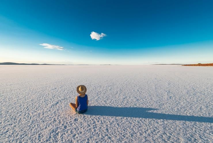 Women wearing a hat sits on the salt flats of Lake Gairdner in South Australia © South Australian Tourism Commission