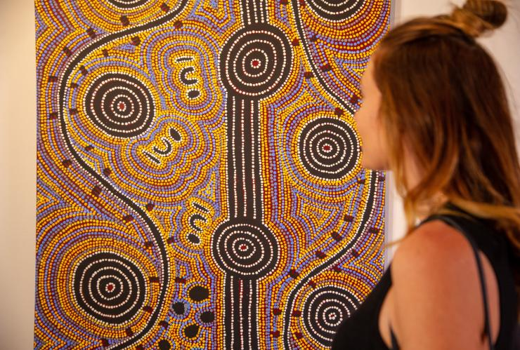 Woman admiring art at Tangentyere Artists in Alice Springs © Tourism NT