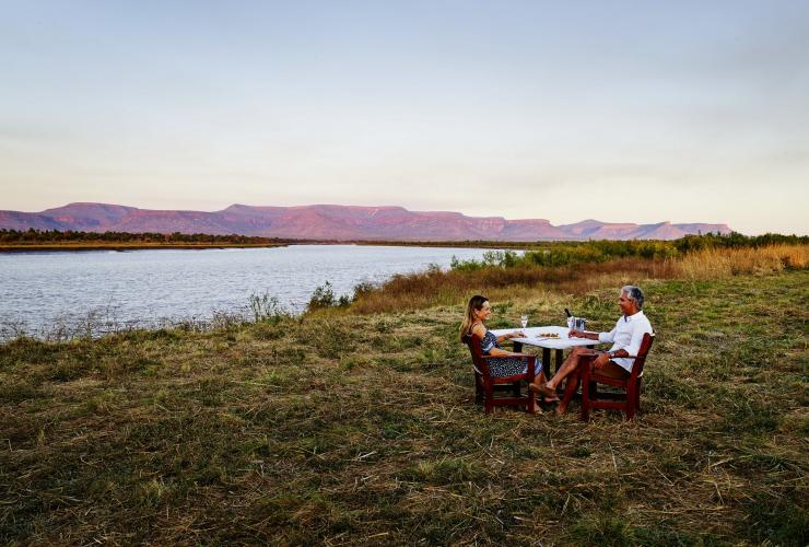Couple enjoying sunset drinks by the Pentecost River with the Cockburn Ranges in the background © Tourism Western Australia