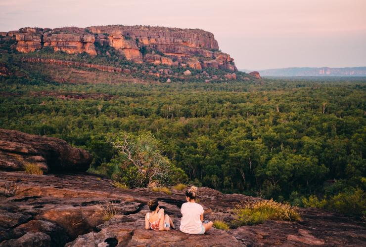 Two people sat on a rock looking at Burrungkuy (Nourlangie) Rock © Tourism NT/Jewels Lynch