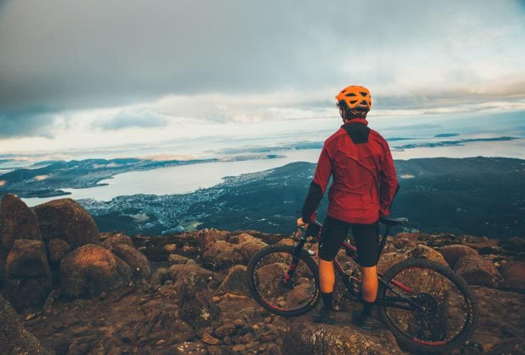 Man with a bike looking out from Mt Wellington in Hobart © Flow Mountain Bike