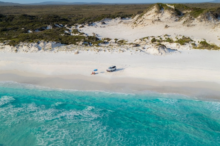 Couple sunbathing on the beach next to 4WD at Cape Le Grand National Park © Australia's Golden Outback