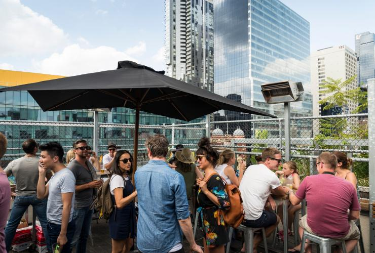 Group of people at Rooftop Bar at Curtin House in Melbourne © Visit Victoria