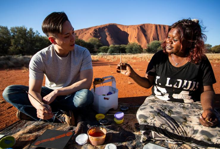 A visitor learning dot painting with a local Aboriginal artist from Maruku Arts inUluru-Kata Tjuta National Park, Northern Territory © Tourism NT/Archie Sartracom