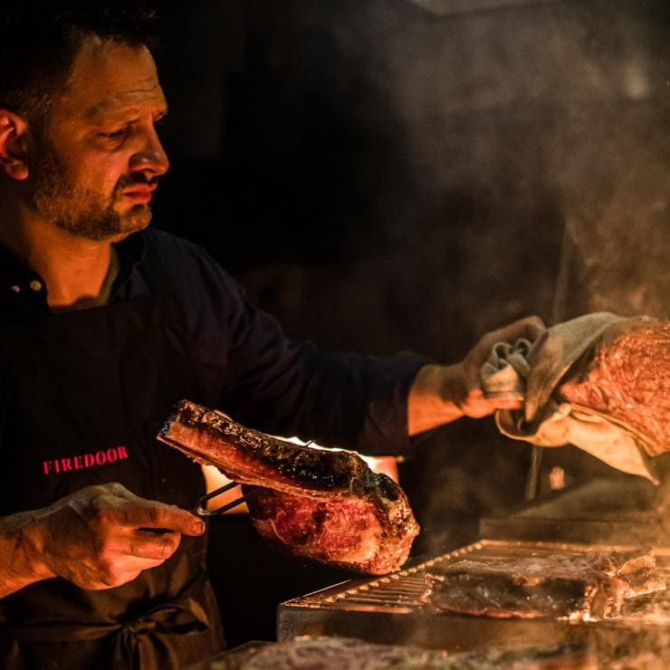 Lennox Hastie cooks a steak over flame © Nikki To