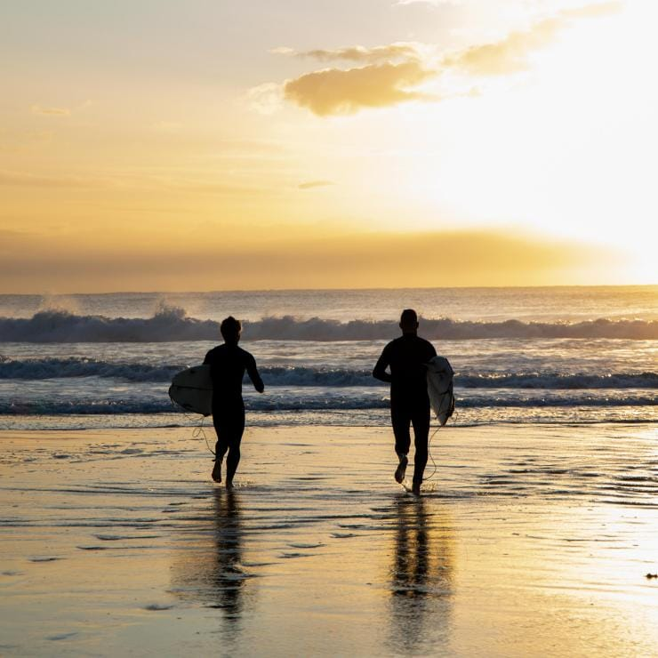 Two men run toward the ocean at sunrise © Boomtown Pictures
