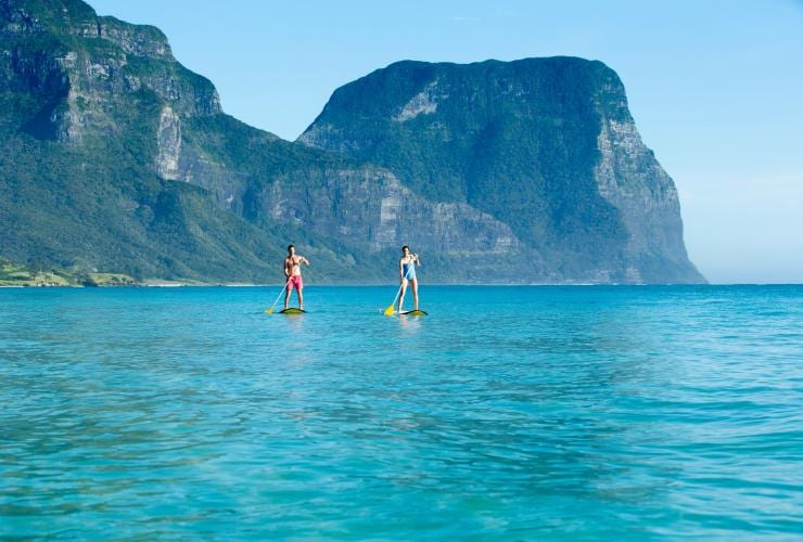 Couple stand-up paddle-boarding at Lagoon Beach on Lord Howe Island © Destination NSW