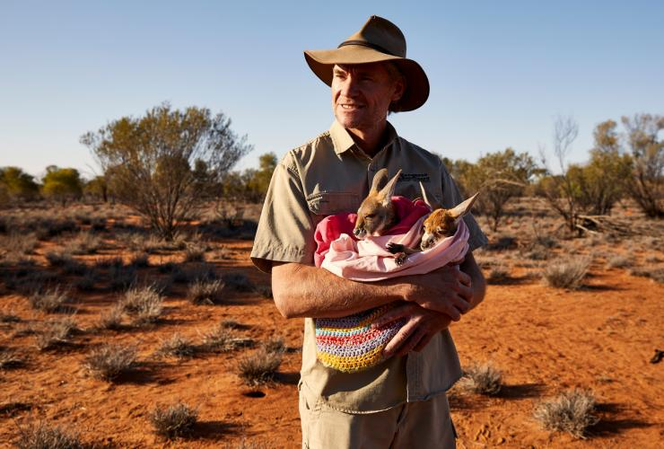 Chris 'Brolga' Barns holding a baby kangaroo at The Kangaroo Sanctuary © Tourism Australia