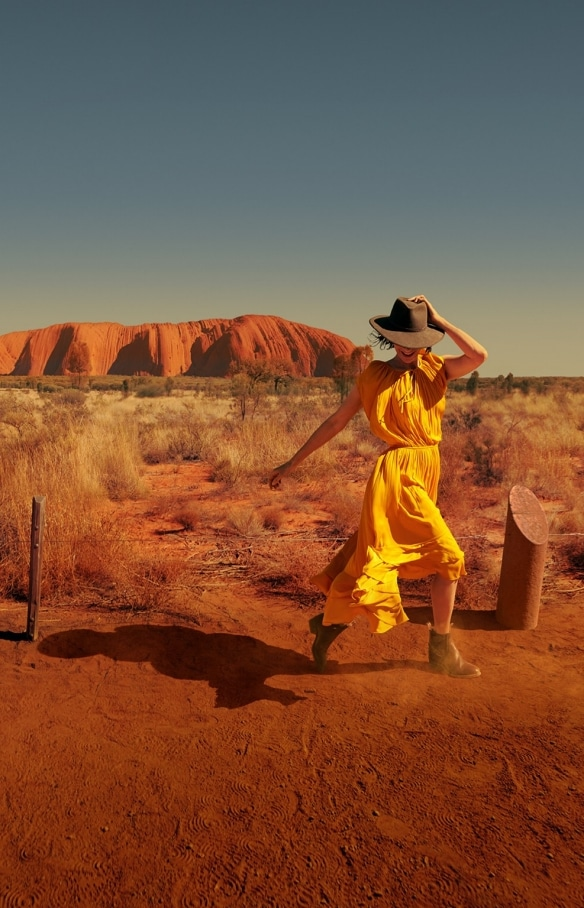 Woman walks around the base of Uluru in Uluru-Kata Tjuta National Park in the Northern Territory © Tourism Australia