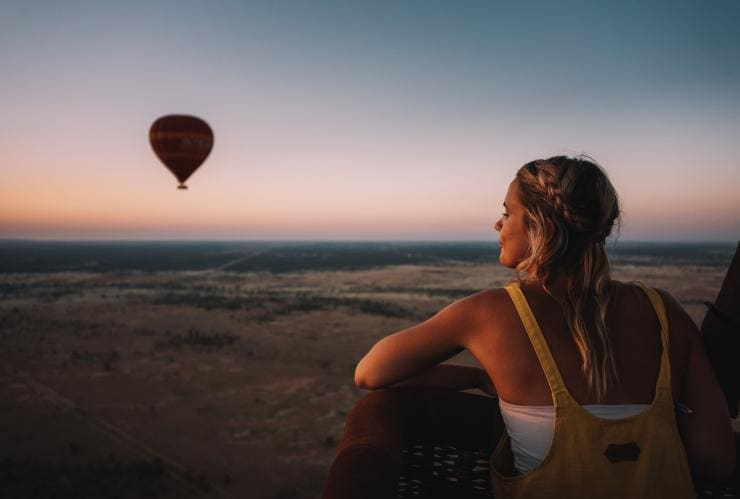 Girl in a hot air balloon looking out over Alice Springs © Tourism NT/Laura Bell 2017